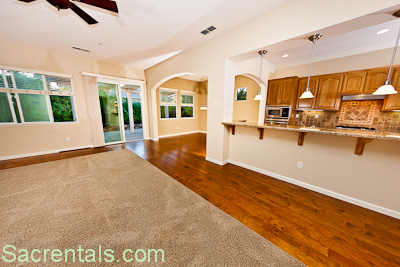 Open Plan Living Room With Double Tall Ceilings Hardwood Border Floors Integrated Carpet Island And Fireplace