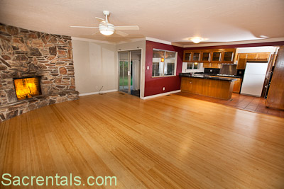 Open Concept Family Room And Kitchen Dining Area With Rock Fireplace Honey Colored Bamboo Wood Floors Access To The Backyard Adjoining Enclosed