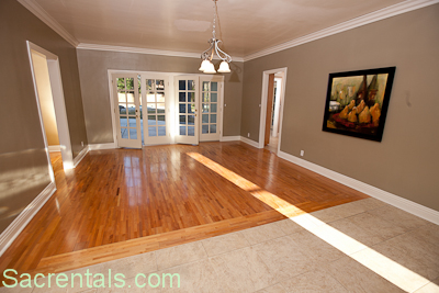 Formal Dining Room With Fireplace View And Cherry Hardwood Floors Looking Towards The Adjoining Kitchen French Doors Open Onto Back Patio